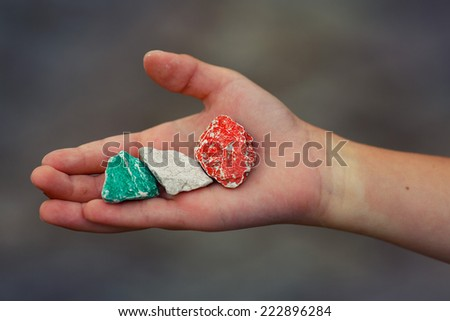 Child hand holding colored stones - colors of the Italian flag - stock photo