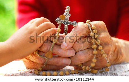child hand holding old catholic woman hand who holds rosary - stock photo