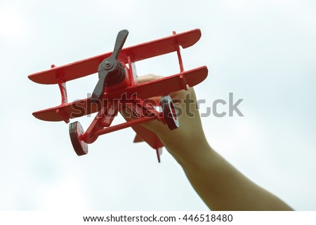 Child hand holding wooden handmade airplane on sky background. Vintage style and focus on propeller.