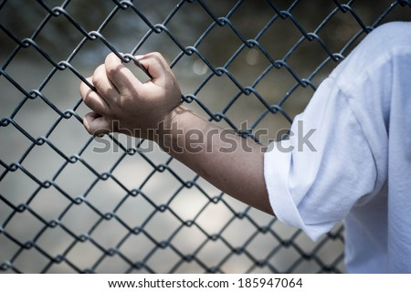 child hand in jail , hand clutching prison,no escape - stock photo