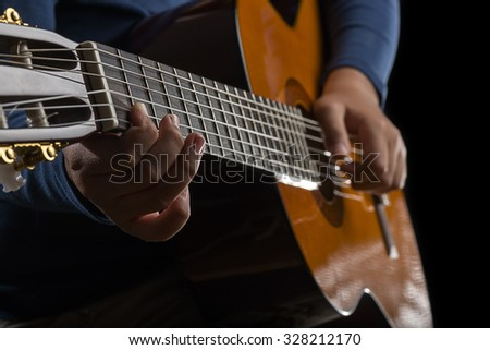 Child Hand Playing Guitar, low key - stock photo