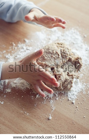 Child hand preparing dough for Christmas cookies - stock photo