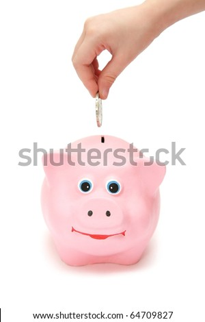 child hand putting a coin into piggy bank