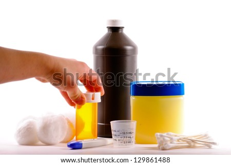 Child hand reaching for prescription medicine on white background. - stock photo