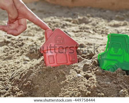 Child hand touches the house toys in the sandbox. Bright plastic toys in the sandbox or on the beach. Sandbox, background, children, hand, home, house, buy, purchase, housing, business. - stock photo