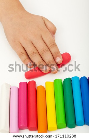 Child hand with colorful modeling clay bars - stock photo