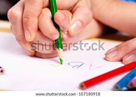 Child hand with pencil and woman hand helping to write letters - stock photo