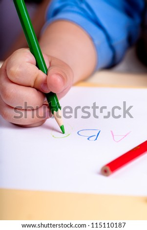 Child hand writing letters with green pencil