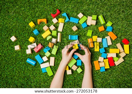 Child hands constructing from color wooden blocks