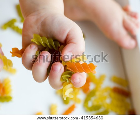 Child hands full of spiral pasta on the white background