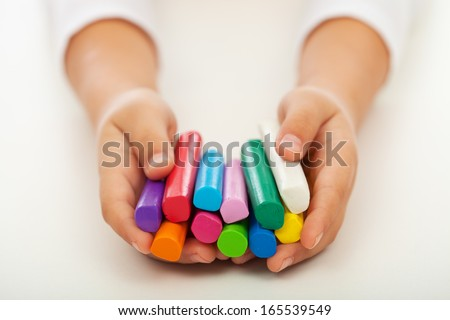 Child hands holding colorful clay bars - closeup