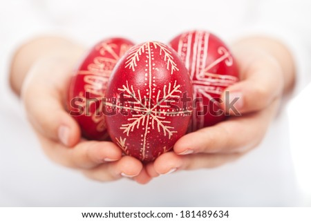 Child hands holding dyed traditional easter eggs with handmade patterns - stock photo