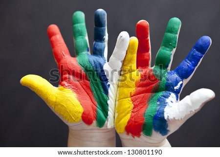 Child hands painted in colorful paints ready for hand prints - stock photo