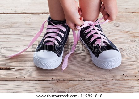 Child hands tie up shoe laces on old wooden floor background