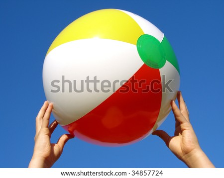 child hands with beach ball against blue sky - stock photo
