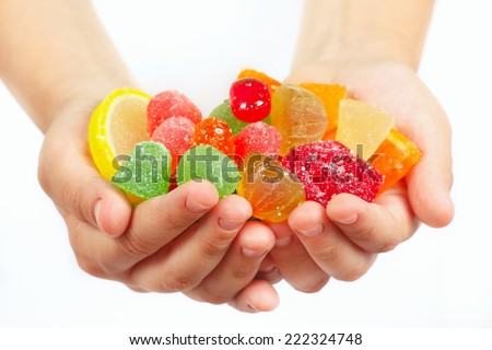 Child hands with colorful fruity sweetmeats and jelly closeup - stock photo