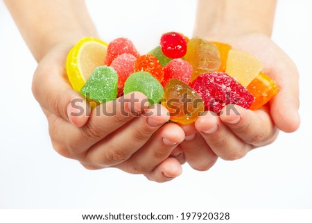 Child hands with colorful fruity sweets and jelly closeup - stock photo