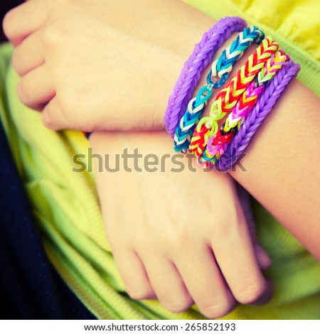 Child hands with Colorful rubber rainbow loom band bracelets, trendy kids fashion accessories.  Vintage retro tonal photo filter correction, instagram style