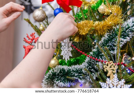 Child hangs Christmas decorations on the Christmas tree. You can see the little girl's hand, colorful lights and other decorations.