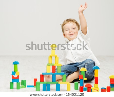 Child happy playing game toy blocks over white background - stock photo