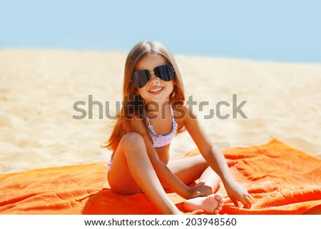Child has a rest in the summer on the beach - stock photo