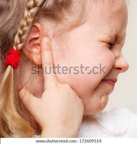 Child has a sore ear. Little girl suffering from otitis - stock photo