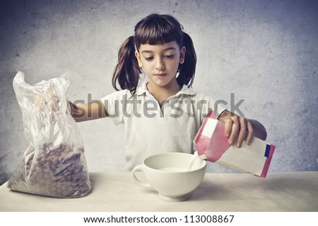 Child having a breakfast with cereals and milk