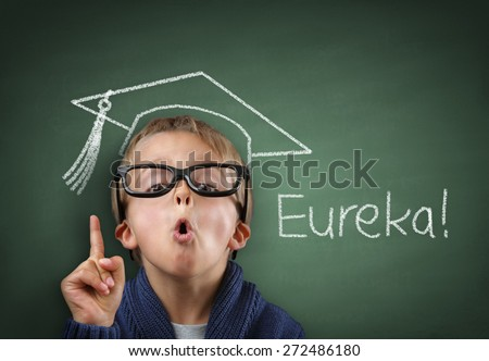 Child having a Eureka moment with mortar board drawing and Eureka on the blackboard concept for genius student, university education and future aspirations - stock photo