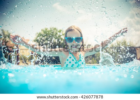 Child having fun in swimming pool. Kid playing outdoors. Summer vacation and healthy lifestyle concept - stock photo