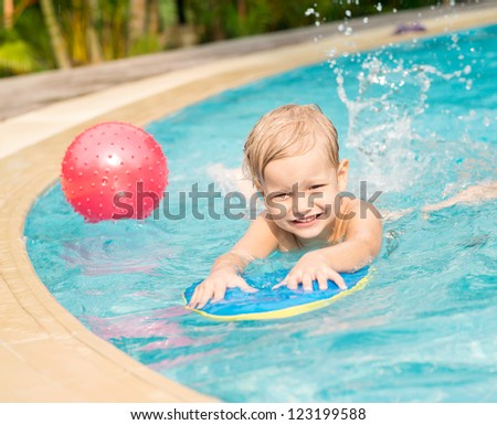 Child having fun in water splashing and playing with a ball - stock photo