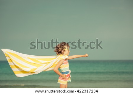 Child having fun on the beach against sea and sky background. Summer vacation and travel concept - stock photo