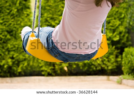 child having fun outdoors at hanging swing