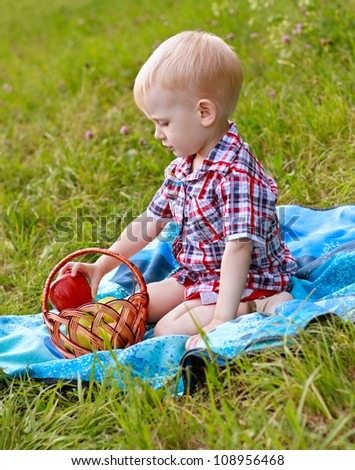 Child having picnic on the green meadow in summer day - stock photo