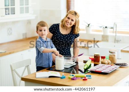 Child helping mother make cookies in modern kitchen