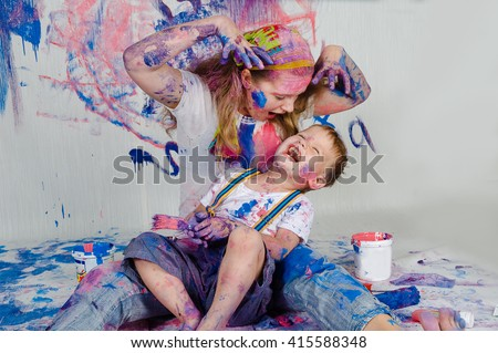 Child himself dirty in the paint and looks into the camera. Child has fun and stain the wall. Children's creativity. Art for baby.