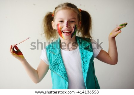 Child himself dirty in the paint and looks into the camera. Girl has fun and painting. Children's creativity. Art for baby. Girl holding a brush in his hand. - stock photo