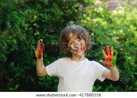 Child himself dirty in the paint and show his dirty hands into the camera. Child has fun and painting / drawing. Children's creativity. Art for baby. Emotions. Delight. - stock photo