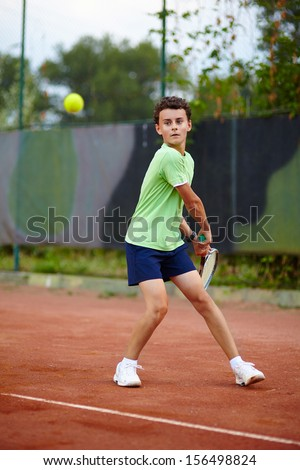 Child hitting the ball with the backhand on a dross court - stock photo