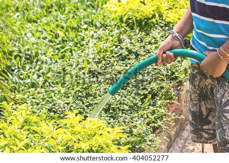child hold spray watering hose in garden on day noon light.