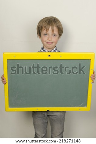 child holding a blackboard back to school on a white background  - stock photo