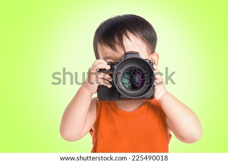 Child holding a camera taking a picture - stock photo