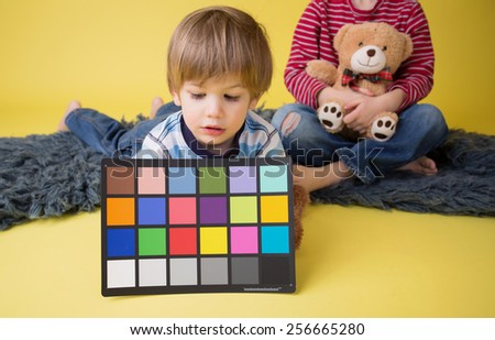 Child holding a custom white balance grey card for a photography session. - stock photo
