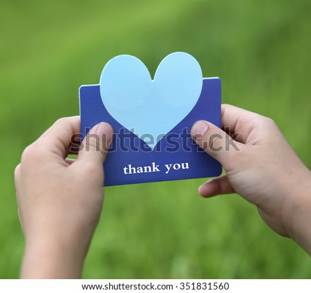 child holding a heart - shaped card  - stock photo