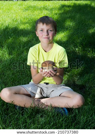 Child holding a  mushroom cep  in hand on a background of green lawn - stock photo