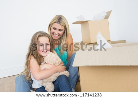 Child holding a teddy bear near her mother in empty living room - stock photo