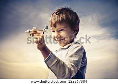 Child holding an airliner in miniature - stock photo