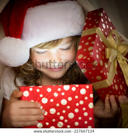 Child holding Christmas gift. Xmas holiday concept - stock photo