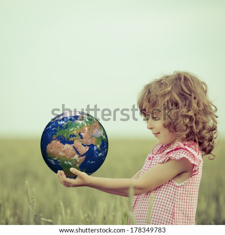 Child holding Earth in hands against green spring background. Elements of this image furnished by NASA