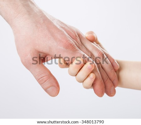 Child holding father's hand, closeup shot on grey background - stock photo