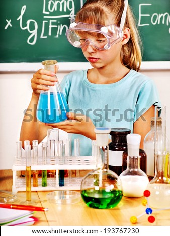 Child holding flask in chemistry class.